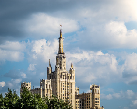 top seven: One of Moscows famous highrises. Blue cloudy sky in background, tree in foreground. Summer in Russia.