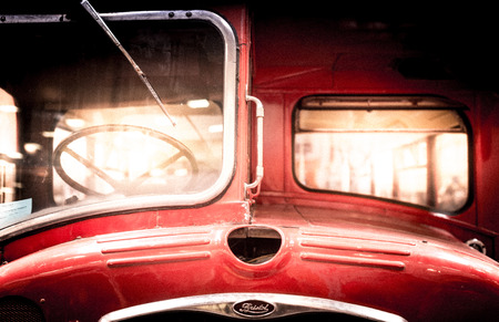 windscreen wiper: Moscow, Russia - March 3, 2013: View of the front bonnet and drivers cab of a restored vintage red double-decker bus showing the badge, steering wheel, single windshield and windscreen wiper. Editorial