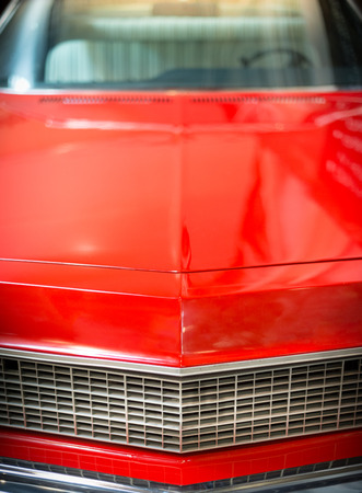shiny car: Close Up Detail of Shiny Red Classic Car with Focus grill and Hood.
