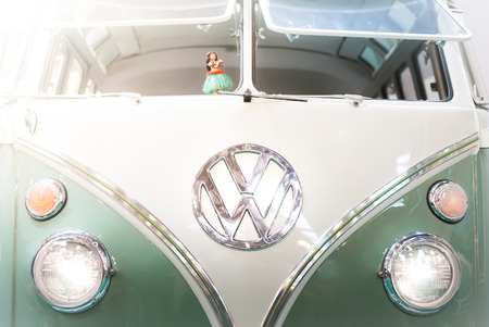 open autocar auto: Moscow, Russia - March 3, 2013: Front view of a green and white 1960s VW campervan with the iconic volkswagen badge and double windshield.