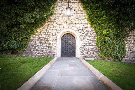 Camino de piedra al viejo hermoso castillo. La luz brillante de la lámpara delante de la puerta, la hierba verde y los árboles alrededor. Hermoso paisaje y un lugar interesante para el recorrido.
