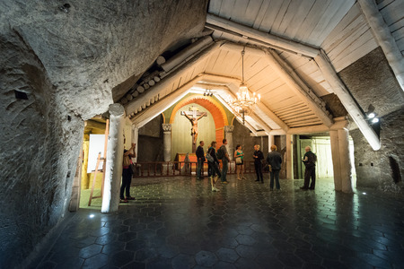 chamber: Krakow, Poland - May 16, 2013. Tourists visiting Wieliczka Salt Mine in Krakow, Poland, Europe. People in underground chamber.