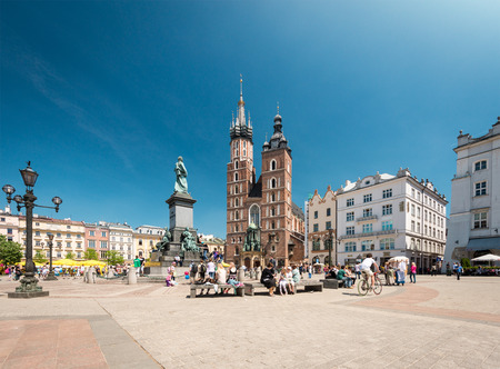 main market: Krakow, Poland - May 16, 2013. Tourists visiting main market square in front of St. Marys Basilica, in Krakow, Poland, Europe. Old medieval  town of Cracow  Editorial