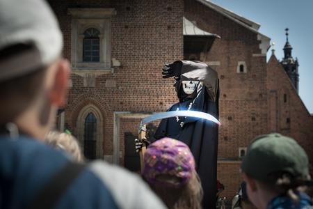 muerte: Actor vestir traje de la muerte en la plaza central de Cracovia, Polonia, Europa. Los niños en primer plano. La muerte está cubriendo su cara con la mano. Sosteniendo guadaña en otra parte. Catedral en el fondo.