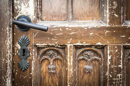 Metal door handle and keyhole on old shabby wooden brown door on house in Krakow, Poland, Europe.