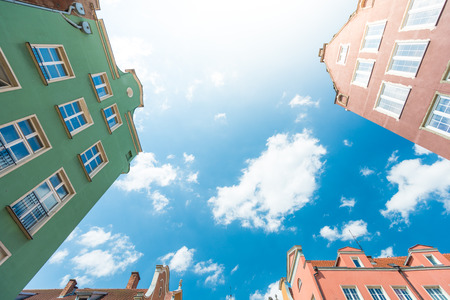 Old and colorful houses in street of Gdansk, Poland, Europe. Beautiful sunny day, blue cloudy sky.