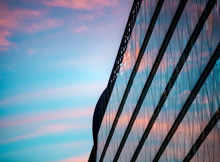 Fachada: la reflexión puesta de sol en los paneles de cristal de un edificio moderno en la parte de Pest de la ciudad de Budapest, Hungría, Europa.