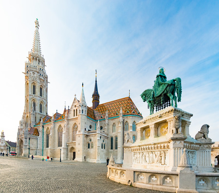 castle district: Old town architecture of Budapest. Buda temple church of Matthias. Budas Castle District. Blue cloudy sky in background statue in foreground. Hungary, Europe.