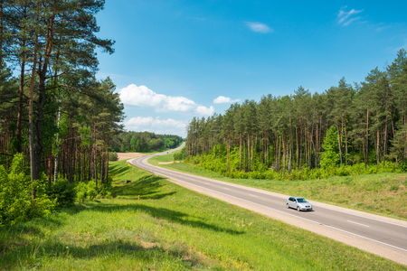 Single car on country road in forest in Belarus. Blue sky with clouds in background.