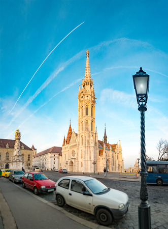 buda: Old town architecture of Budapest. Buda temple church of Matthias. Budas Castle District. Blue cloudy sky in background and parked cars in foreground. Hungary, Europe.