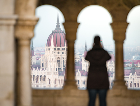 fisherman bastion: View on parliament building from fisherman bastion on Buda hill. Budapest, Hungary, Europe travel. Unrecognizable tourist in foreground taking photo.