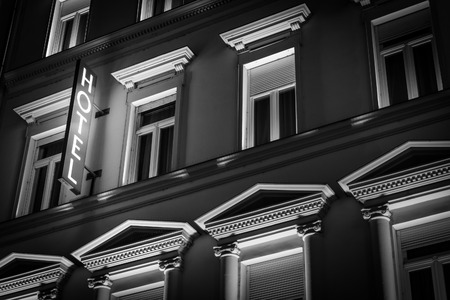 Glowing hotel sign in night on old building. Architecture of Budapest, Hungary, Europe, travel.