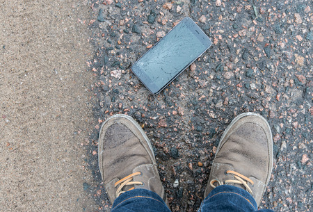 cellular telephone: Phone with broken screen on asphalt. Someone dropped device.