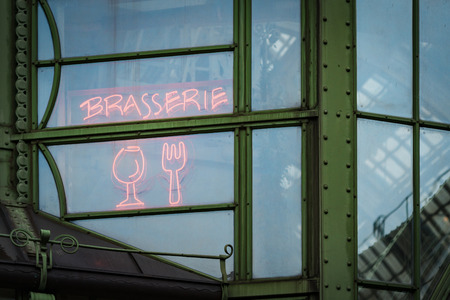 brasserie: Details of street cafe in Vienna, Austria. Window with neon sign inscription brasserie, glass and fork. Europe travel.
