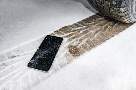 Phone with broken screen on snow in car trail. Glass covered with snow flakes. Device run over by wheel. Stock Photo