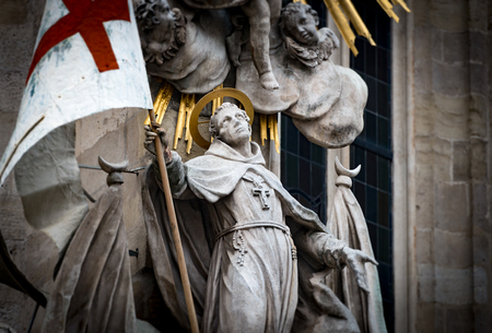 europe travel: Close up view on one of statues at St Stephens Cathedral in Vienna, Austria. Saint holding flag with red cross. Europe travel.