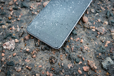 Phone with broken screen on asphalt. Someone dropped device. Glass covered with snow flakes.