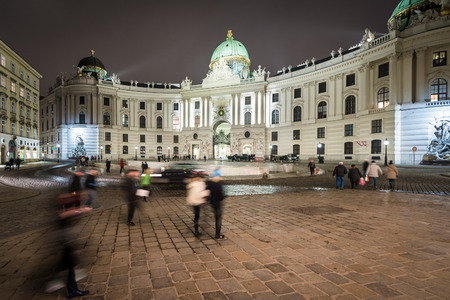 europe travel: Hofburg Palace in centre of Vienna. Official residence and workplace of Austria President. Night scene with tourists walking near building. Europe travel.