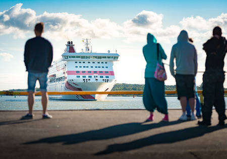 turku: Big ferry ship arriving in port of Turku, Finland, Scandinavia, Europe. Liner with blue cloudy sky in background and people waiting in foreground. Stock Photo