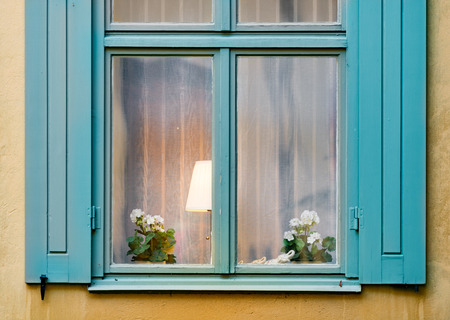 old house window: Details of old house window with flower and lamp inside. Yellow wall of building. Stockholm, Sweden, Scandinavia, Europe. Editorial
