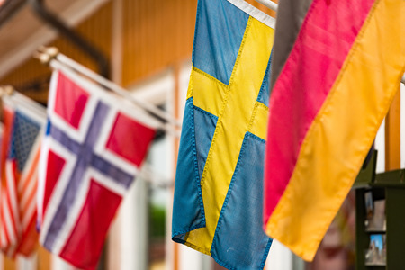 bandera de suecia: Many flags on wall of building in old town Sigtuna. Europe travel. Sweden, Scandinavia.