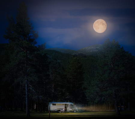 Recreational vehicle at night in Norway, Europe. Hills and dark cloudy sky with full moon. Travel by RV. Nordic country, Europe, Scandinavia.