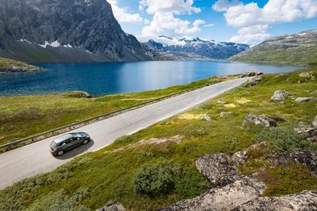 ヨーロッパ ノルウェーの山の中の車。自動スカンジナビアの旅。青い曇り空、背景にある湖。 写真素材