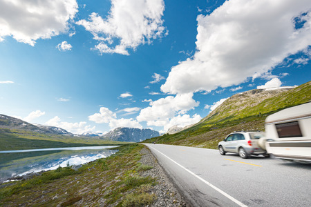 Car with RV trailer in mountains of Norway, Europe. Auto travel through scandinavia. Blue cloudy sky and lake in background. Stock Photo