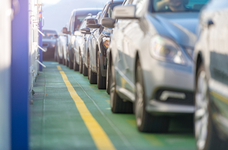 Cars waiting in line on deck of ferry in Norway, Scandinavia, Europe. Water transportation. Stock Photo