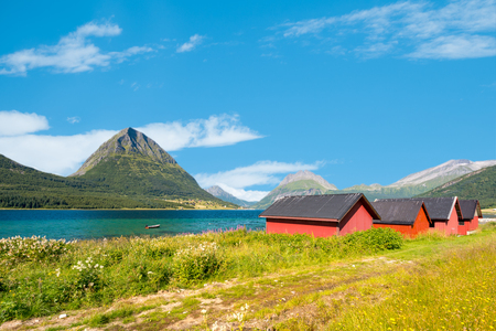Beautiful landscape of Norway. Red barns, lake and meadows, mountains and cloudy sky in background. Travel in Scandinavia, Europe