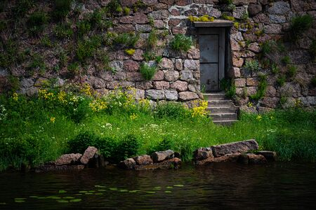 Architecture of old town Vyborg, Russia, Europe. Old door and Vyborg castle wall on with river and grass
