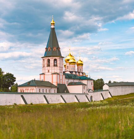 Monastery with bell tower and golden church domes. Meadow and wall in foreground with blue cloudy sky in background
