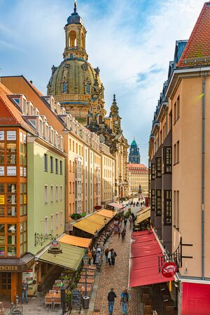 DRESDEN, GERMANY - SEPTEMBER 22, 2014: Old street with Frauenkirche cathedral in Dresden, Germany. Church of Our Lady is a Lutheran church in state of Saxony. View from square with people walking around Editorial