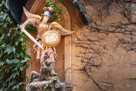 Statue of angel with sword and shied fighting devil in The Fuggerei walled enclave within the city of Augsburg, Bavaria, Germany