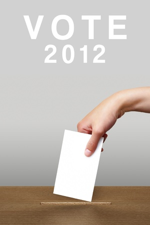 Hand putting a voting ballot in a slot of wooden box on white background, Vote 2012 Stock Photo - 12861332