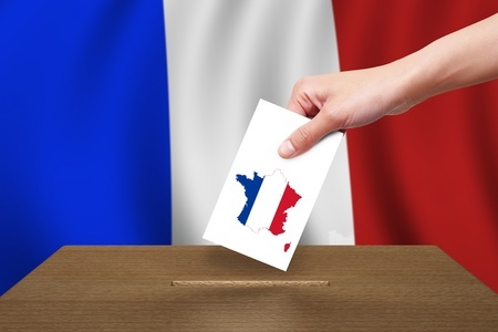 Hand with ballot and wooden box on Flag of France photo