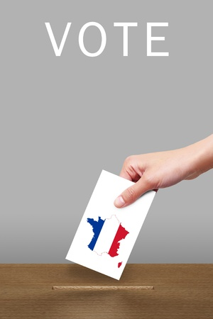 Hand with ballot and wooden box on Flag of France Stock Photo