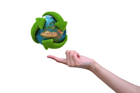sustainable development: Globe with green arrows covered with grass presented on female finger