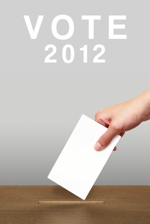 Hand putting a voting ballot in a slot of wooden box on white background, Vote 2012 photo