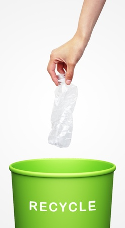 hand putting a plastic bottle into a recycling bin  Stock Photo
