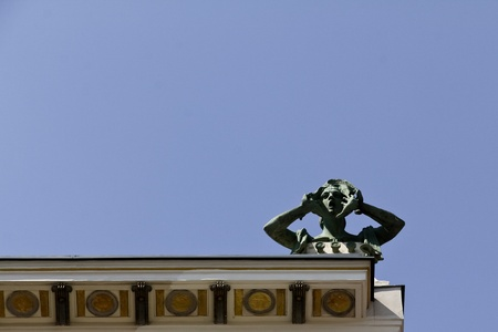 An art nouveau building with a screaming sculpture on top in Vienna photo