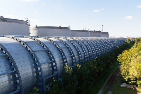 A noise barrier of a road from behind next to an industrial area with silos Stock Photo - 10922027