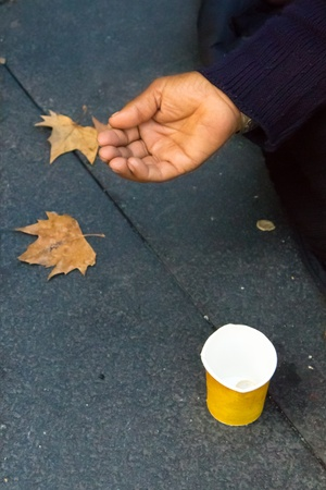 A hand begging for money on a street in Madrid photo