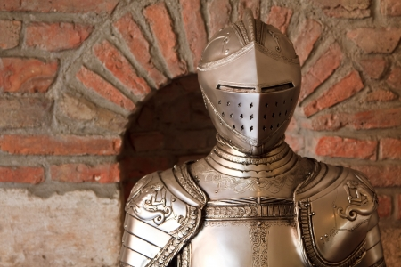 A knights armour with shining metal and ornate shield and sword photo