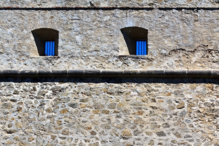 iron barred: An old jail wall with windows into the blue sky on castle Forchtenstein