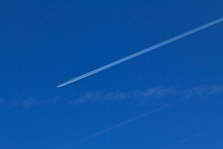 A plane on blue sky and its contrail in the afternoon in Austria photo