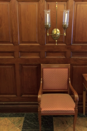 A classic chair in front of a wood panel in a hotel lobby photo