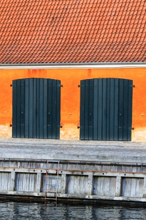 A garage in an orange building next to a small river photo