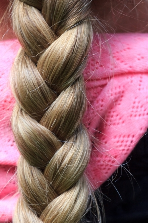 A blond long and thick braid of a woman Imagens