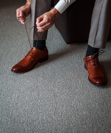 A young man tying elegant shoes indoors photo